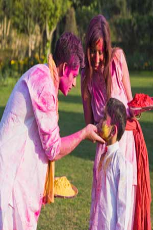 Family playing Holi with natural colours