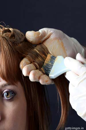 Hairdresser applying hair colour to woman