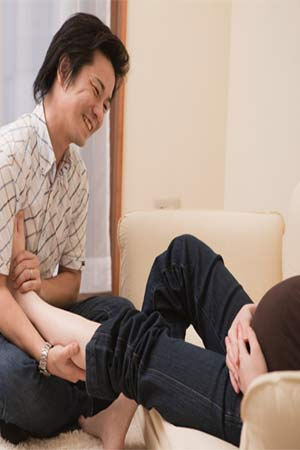 husband massaging pregnant wifes feet