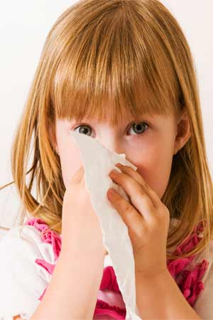 little girl wiping nose with handkerchief