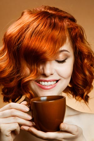 Woman smiling at a cup of coffee