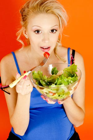 Beautiful pregnant woman eating salad from a bowl