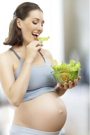 Pregnant woman eating a bowl vegetarian salad