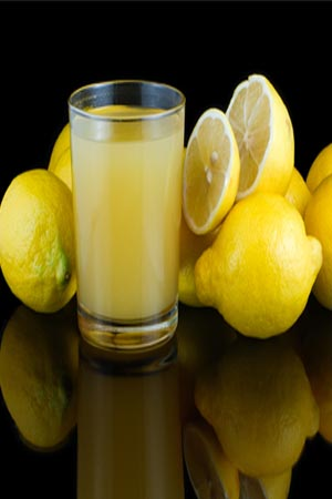 Lemons surrounding  a glass of lemon juice