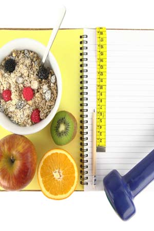 healthy food with dumbbell and measuring tape