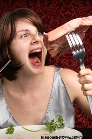 Girl eating steak with large utensils