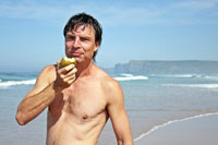 Man having apple on the beach